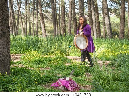 Female shaman drumming and chanting with altar