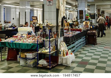 Moscow, Russia - March 19, 2017: Old items from the last century on sale at the flea market. Table and shelves with vintage Christmas decorations and toys in the foreground.