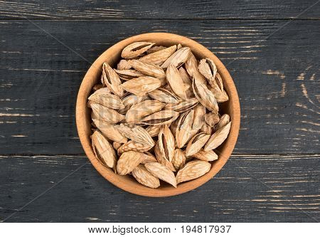 Uzbek inshell almonds in a bowl on wooden background, top view