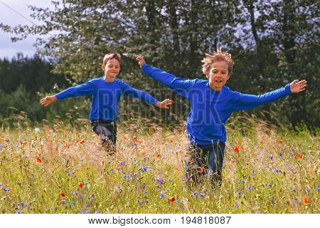 Happy kids running and jumping on beautiful meadow field.