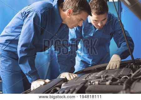 Professional look. Two prominent local specialists looking under the bonnet of a car and examining its mechanisms while repairing it in garage