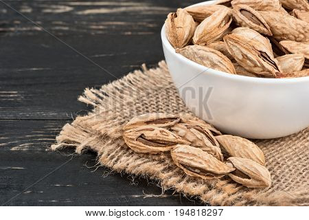 Uzbek inshell almonds in bowl on a burlap and wood background closeup