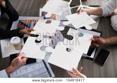 Team of businessmen work together for one goal with puzzles. Concept of unity and partnership
