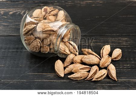 Scattered uzbek almonds from a jar on a dark table