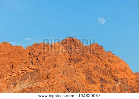 the full moon rising over the red rock landscape of the valley of fire state park Nevada