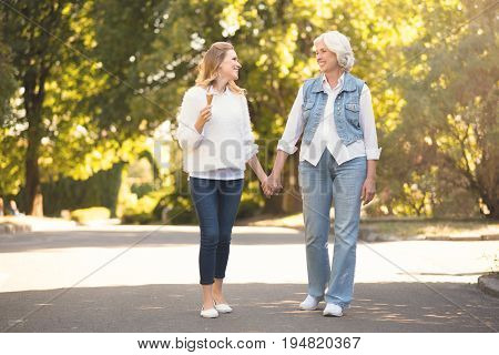 Spending active weekend . Happy greyish old mother enjoying the sunny weather outdoors while expressing joy and holding hands with mature daughter