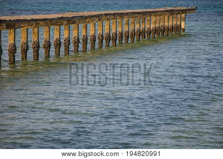 Beachfront atmosphere in the morning on the shore With wooden bridge extends into the sea.