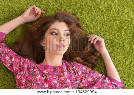 Beautiful young woman lying on green carpet