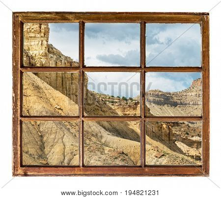 cliff, buttes and mesa of Book Cliffs in eastern Utah as seen  through vintage, grunge, sash window with dirty glass