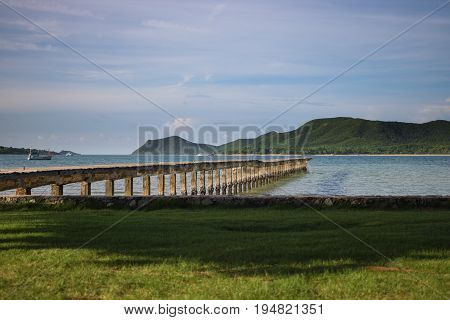 Beachfront atmosphere in the morning on the shore With green grass And the wooden bridge extends into the sea.