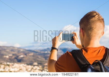 Travel, vacation, photographer and hitchhiker concept - raveler man photographed mountains and city in the smartphone.
