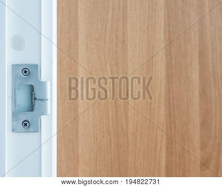 Metal socket for door knob on the white PVC frame of the living room.