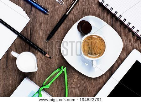 Coffee Break Concept with Stationery Items Coffee Cup with Milk Jug Digital Tablet and Greens Eyeglasses closeup on Wooden background. Top View
