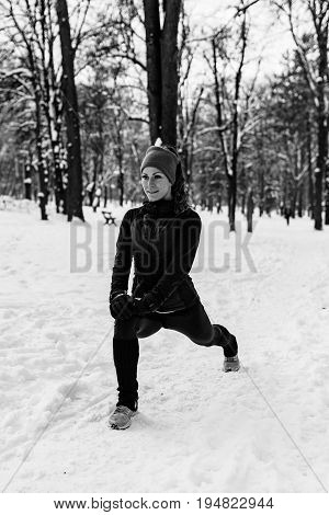 Female Athlete Exercising In Park In Winter, Black And White