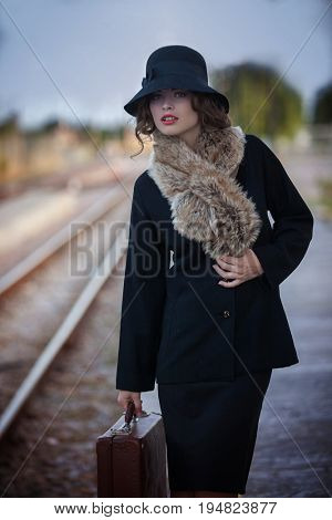 retro woman with case at railway station