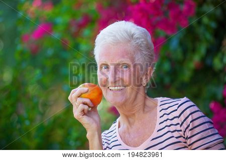 healthy senior woman with white teeth eating apple.