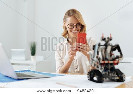 Observing tech progress. Delighted friendly charming woman using digital gadget and taking pictures while looking at electronic robot