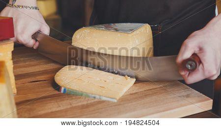Cutting hard cheese, pecorino cheese in grocery shop, closeup