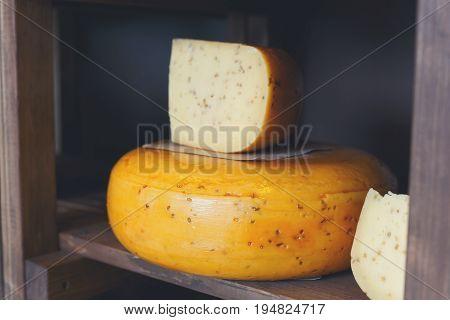Gouda pesto cheese as wheel and piece on grocery shop wooden shelf, closeup