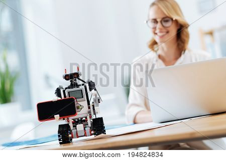 Mastering human skills. Futuristic automatic funny robot standing on the table in the office and holding digital gadget while engineer using laptop on the background and smiling