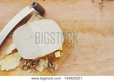 Cheese platter. Goat milk cheese in piece and slices on natural wood disc with nuts, still life, closeup