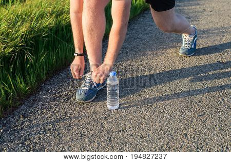 Running shoes. Barefoot running shoes close up. male athlete tying laces for jogging on road. Runner ties getting ready for training. Sport lifestyle