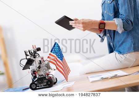 Typical American workplace of the future. Skillful young involved woman sitting in the office and taking pictures while using tablet and interacting with self automated robot