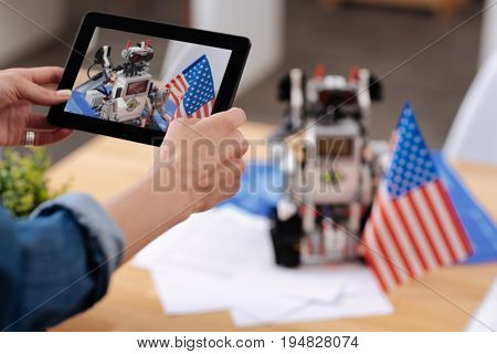 Proud inventor of new robot system. Intelligent young professional engineer woman standing in the office and taking pictures while using tablet and enjoying electronic robot