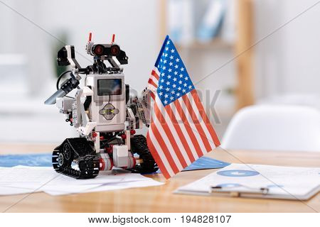 Proud to be made in America. Futuristic cute modern robot standing on the table in the office and holding American flag while symbolizing new tech epoch