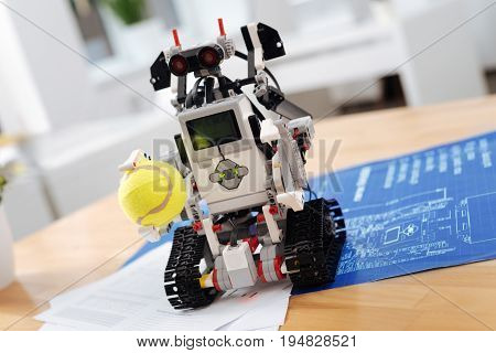 Lets play. Technological futuristic smart robot standing on the table in the laboratory and holding tennis ball while symbolizing new tech invention