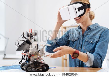 In the parallel world. Smiling happy joyful woman sitting in the lab and using visual reality glasses while enjoying electronic robot