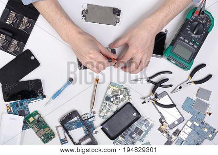 Mobile phone repair at service center, smartphone dissasembling and diagnostic, repairman workplace top view