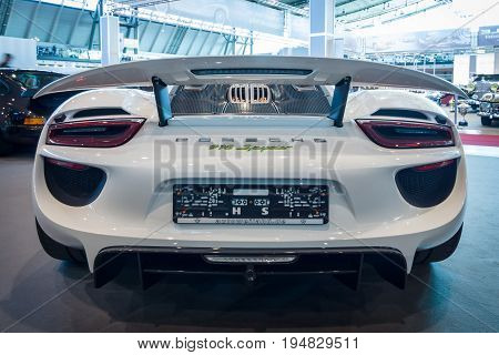 STUTTGART GERMANY - MARCH 17 2016: Mid-engined plug-in hybrid sports car Porsche 918 Spyder 2015. Rear view. Europe's greatest classic car exhibition