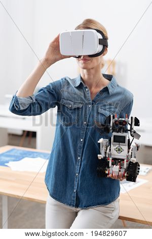 Enjoying virtual environment . Busy skilled concentrated woman taking part in the tech experiment and testing visual reality headset while holding little automatic robot