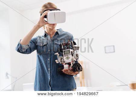 Enjoying multi projected environment. Concentrated inspired young woman taking part in the tech experiment and using visual reality headset while holding little electronic robot