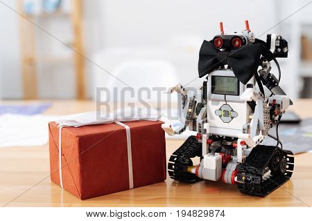Here for you. Cute stylish romantic robot standing on the table and wearing bow tie while looking like a gentlemen and touching gift box