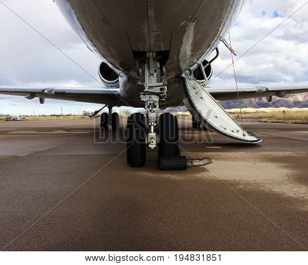 This photo consists of a landing gear of a Private Jet which is taken from the front of the airplane. Also contains a good view of the wings and the jet engines. With its door open it urges you too come on board!!