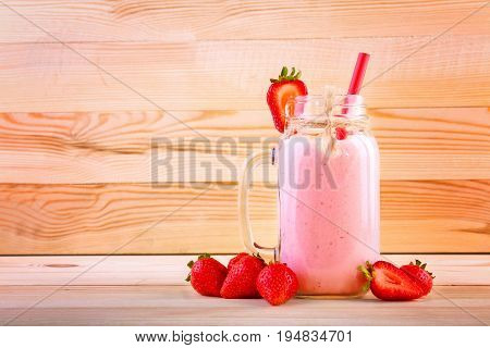 A glass jar with strawberry smoothie on a large light brown wooden table. The big, thin and straight red straw in the jar with beverage. A few strawberries are near a full jar of strawberry drink.