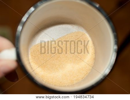 Heap Of Dry Small Gelatine Granules Or Powder In A Mug, Top View