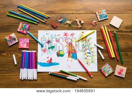 Crayons, felt-tip pens and a child's drawing on a wooden table.