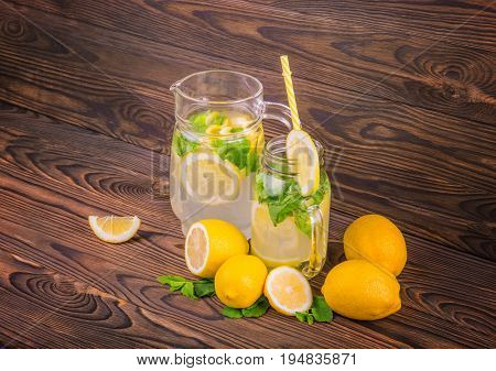 A big glass jug with lemon juice, a glass and lemons stand on a dark brown wooden, table isolated on a white background. A long yellow straw and a slice of lemon is in a beautiful glass.