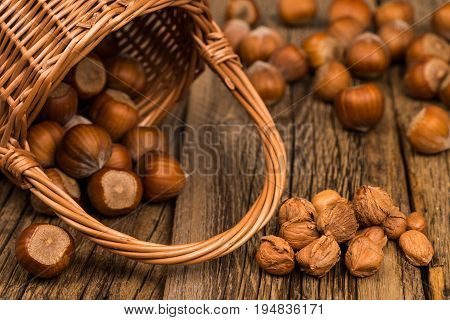 Hazelnuts in a basket on old wooden table. selective focus.