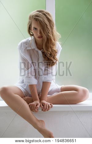 Passionate curly blonde with exquisite make up wearing seductive transparent shirt posing at camera on window studio shot