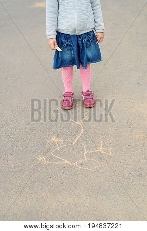 Four-year-old girl staying with a piece of chalk on asphalt over her drawing. Her face is not seen.