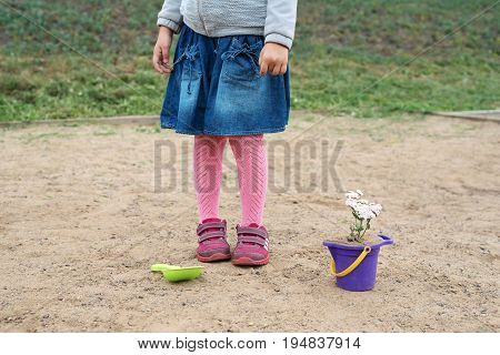 Little girl playing in a sand-box on a cloudy summer day She is planting a flower in a toy bucket. Her face is not seen.
