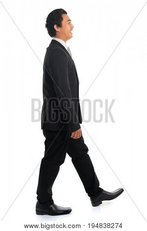 Full length side view of handsome young Southeast Asian businessman walking, isolated on white background.