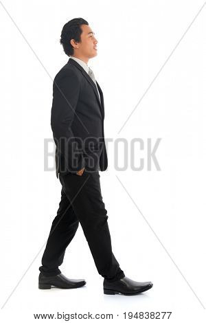 Full length side view of good looking young Southeast Asian businessman walking, isolated on white background.