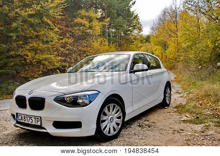 Plovdiv Bulgaria 18.10.2014: front side view of a white color BMW car parked beside the road in an autumn forest
