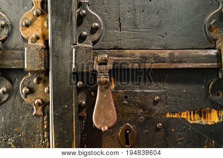 aged ancient wooden door with vintage metal latch in Matera south Italy.