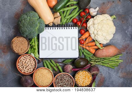 Top view of vegetables and grains, arranged in a circle with white notebook in the middle, broccoli, squash, beans, tomatoes, carrots, avocado, top view, selective focus